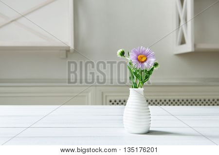 Aster amellus flowers bouquet in white ceramic vase at wooden table. White shabby chic interior. Flower detail in interior design. Purple aster in vase. Violet Aster bouquet at home