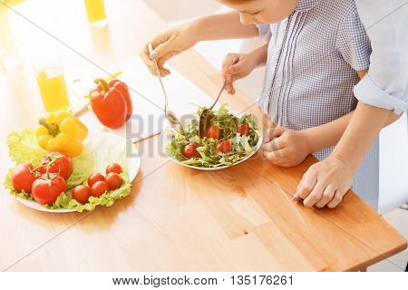 Start healthy eating at ayoung age. Top view of mother and daughter mixing vegetable salad in dish