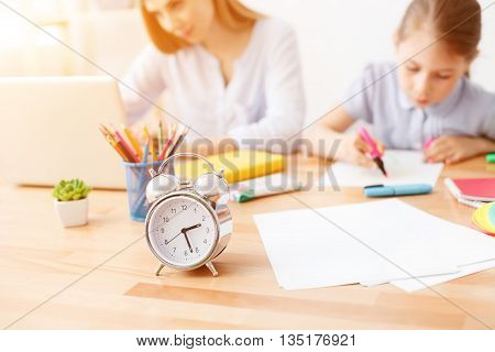 Painting play time. Close up of alarm clock staying on desk with mother and daughter painting in background