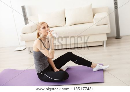 Her secrets to vitality. Sporty young woman holding bottle of water and drinking during doing yoga at home