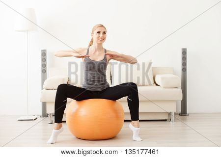 The fit life. Sporty young woman sitting on swiss ball doing stretching exercises at home