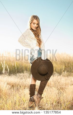 Beautiful Young Lady Model Posing In A Field At Sunrise With A Hat In Hand