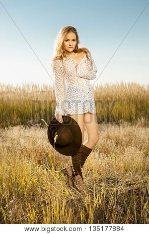 Beautiful Young Model Posing In A Field At Sunrise With A Hat In Hand