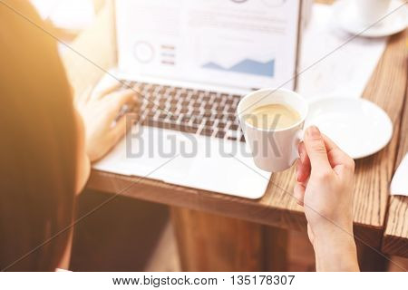 Concept of busy businesswoman using laptop while drinking coffee. Focus on cup