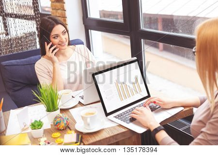 Joyful young woman is talking on mobile phone and smiling. She is sitting at table in cafe. Her colleague is typing on laptop with concentration
