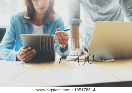 Coworkers team brainstorming process in modern office.Project producer reading report tablet, glasses wood table.Young business crew working with startup studio.Using Laptop. Blurred, film effect