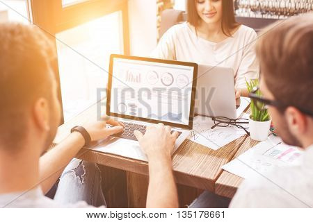 Cheerful creative team is working on project together. Man is typing document on laptop with concentration. Woman is sitting at table and smiling
