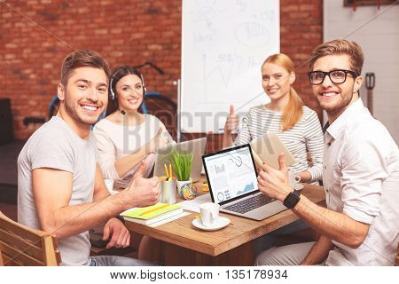 Everything is okay. Successful four colleagues are giving thumbs up and smiling. They are sitting at desk in office. Men and women are looking at camera happily