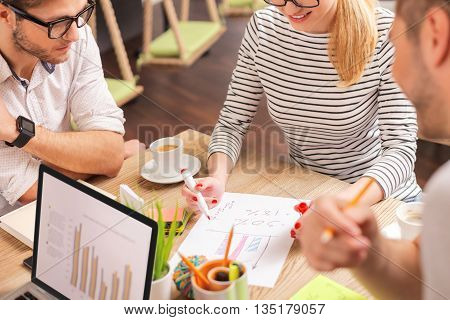 Smart colleagues are discussing a project. They are sitting at desk and smiling. Woman is drawing a diagram with aspiration