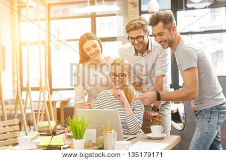 Cheerful young colleagues are planning new project. They are standing and looking at laptop with joy. Woman is sitting at desk and smiling