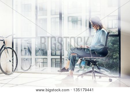 Hipster Girl using Laptop huge Loft Studio.Student Researching Process Work.Young Business Woman Working Creative Startup modern Office.Analyze new marketing strategy.Blurred, film effect.Horizontal