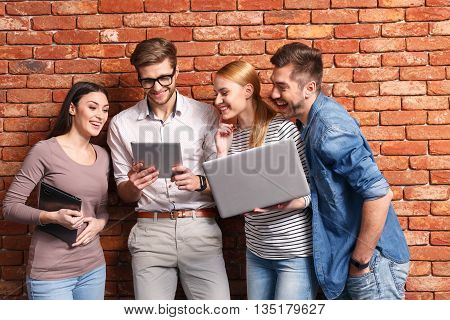 Cheerful young students are entertaining themselves with contemporary technology. They are standing and looking at tablet with interest. Woman is holding laptop. Man is smiling
