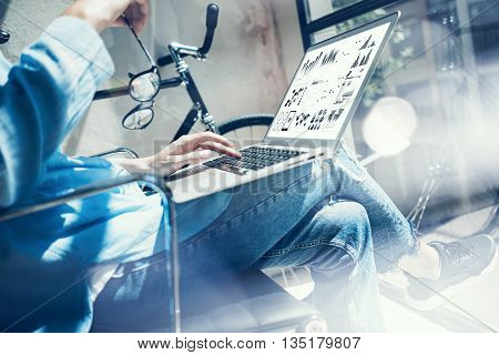 Work process modern design Studio Loft.Creative director working coworker office new freelance business startup.Using Laptop graphs, diagram, charts screen.Horizontal.Flares, reflections effect.Blurred