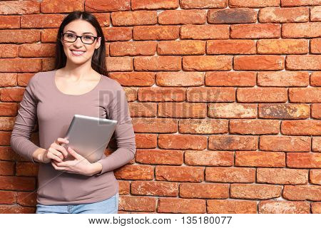 Successful young businesswoman is holding a notebook. She is looking at camera and smiling. Woman is standing and leaning on the wall. Copy space in right side