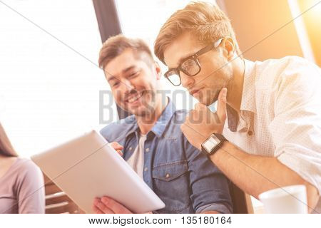 Smart two colleagues are working on project together. Man is sitting and showing a tablet. His friend is looking at technology pensively