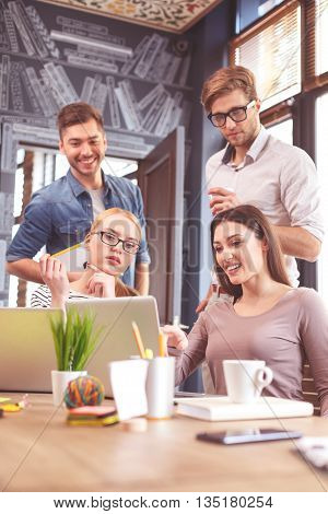 Joyful young colleagues are discussing a project in office. Women are sitting at desk and looking at laptop with interest. Men are standing and smiling