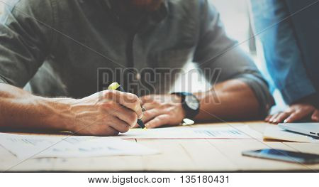 Coworkers team.Analyzing stock reports process modern design loft.Project manager makes notes marker.Creative business crew working new startup.Devices wood table.Blurred, film effect. Closeup photo
