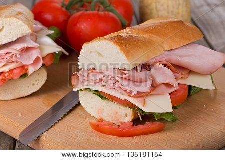 Fresh ham and cheese sandwich with lettuce and tomato on French bread