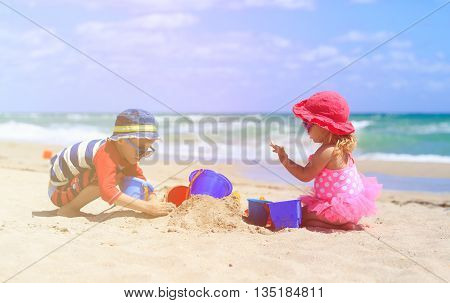 kids play with sand on summer beach, family vacation