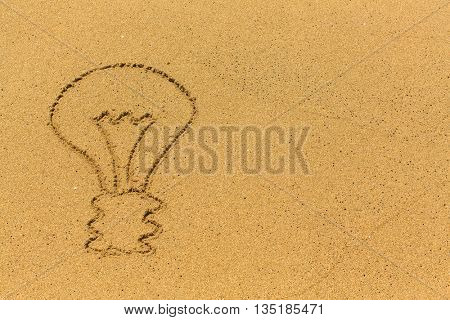 Light bulb drawn in the sand.
