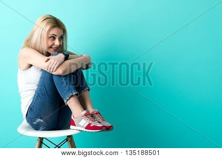 Beautiful shy blond girl is looking forward with anticipation. She is sitting on chair while embracing her legs. The lady is smiling. Isolated and copy space in right side