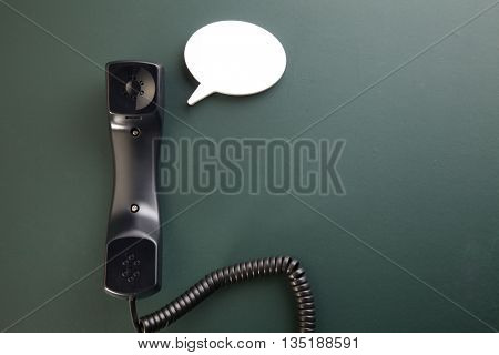 handset with speech bubble on the blackboard