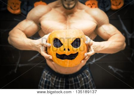 gym halloween theme gym halloween gourd bodybuilder with pumpkin in his hands, a strong man squeezes a pumpkin, sportsman's trunk, strong hands squeeze Halloween pumpkin