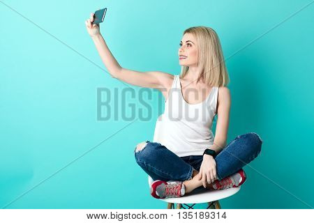 Beautiful blond girl is making selfie on a mobile phone. She is sitting on chair and posing. The lady is smiling. Isolated and copy space in left side