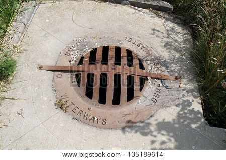 NAPERVILLE, ILLINOIS / UNITED STATES - JULY 23, 2015: A storm drain cover urges people to dump no waste, because it drains to waterways.