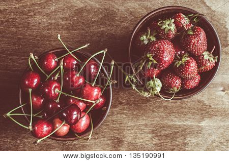 Fresh ripe organic cherries and strawberry on wooden background. Vintage rustic style and color tinting. Selective focus.