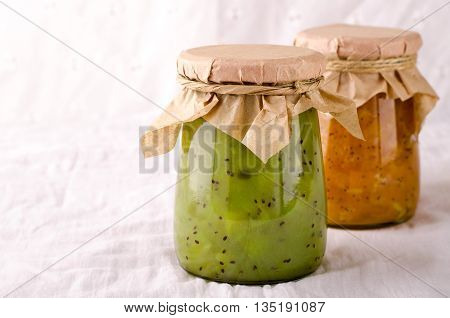Pumpkin-Orange-Ginger-Poppy seed and Kiwi-Mint homemade jam on white background.