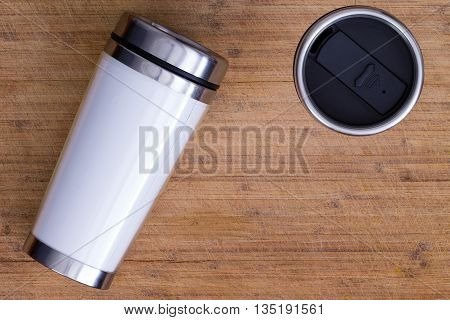 Top down view on pair of blank white and stainless steel thermos laying down and standing up over smooth brown wood surface with copy space