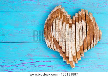 Sliced Bread Shaped As Heart On Old Blue Table