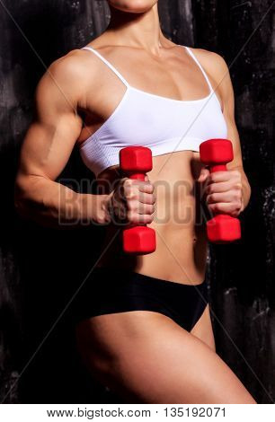 Strong woman with red barbells, dark background