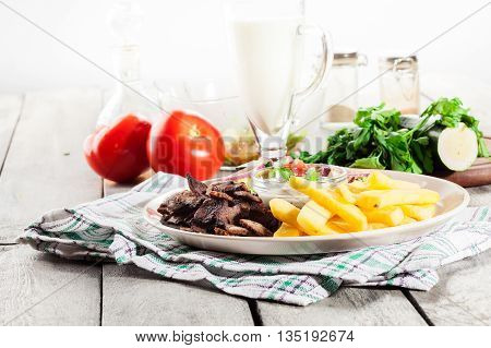 Grilled Meat With French Fries And Fresh Vegetables