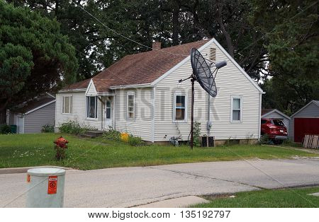 SHOREWOOD, ILLINOIS / UNITED STATES - AUGUST 30, 2015: A small Cape Cod style home, with a large satellite dish, in Shorewood, Illinois.
