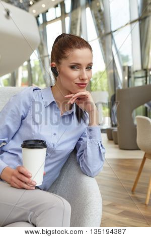 Coffee break. Pleasant modern attractive young woman holding mobile phone and sitting at the table while relaxing in the cafe