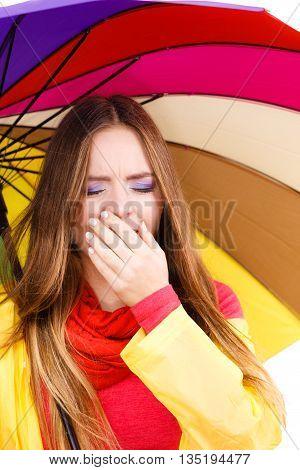 Woman Under Umbrella Sneezing