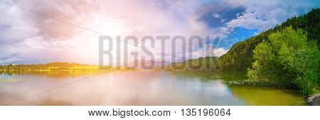 Lake in the German Alps with a chain of mountain peaks on the horizon. Sunrise or sunset