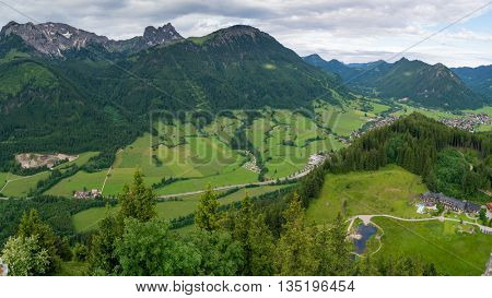 The village is in an alpine valley. Green fields in the mountains