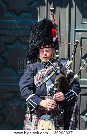 EDINBURGH SCOTLAND - MAY 29 2016: A Scotsman wearing traditional Scottish outfit playing the bagpipes along the Royal Mile in Edinburgh on 29th March 2016.
