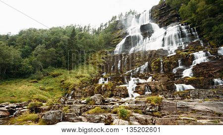 Panorama of Tvindefossen Waterfall in Norway. Norwegian nature landscape at summer. Waterfall Tvindefossen is largest and highest waterfall of Norway, its height is 152 m.