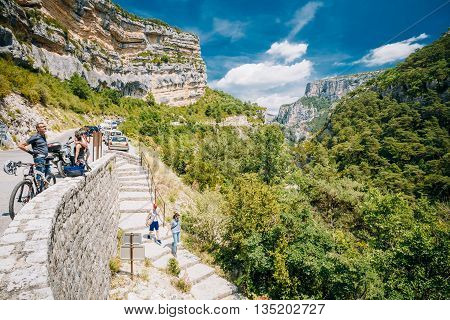 Verdon, France - June 29, 2015: Tourists descend the stone steps to the mountain river Le Verdon in the Verdon Gorge in south-eastern France. Provence-Alpes-Cote d'Azur.