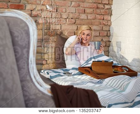 Young woman talking on mobilephone while having breakfast in bed in the morning.