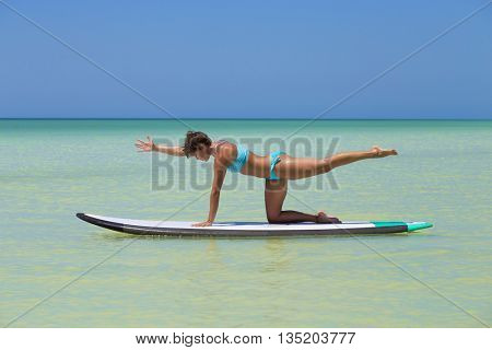 Woman practicing SUP yoga, on a paddleboard in the Caribbean