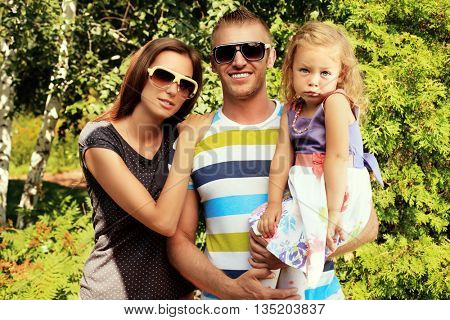 Happy parents with their adorable little daughter. Outdoors. Sunny summer day.