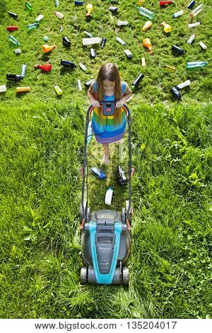Illusion of progress and development - young girl cutting grass and leaving plastic litter behind