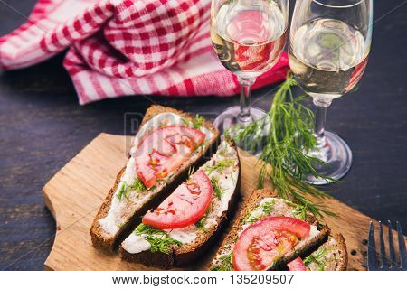 sandwich from dark bread and fresh tomatoes on old wooden board