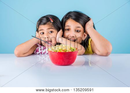 Happy Asian children eating delicious noodle, two cheerful little indian girls eating noodles in red bowl over blue background, two indian little sisters or friends with noodles