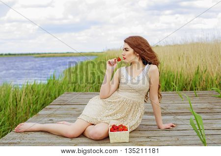Pretty girl on river quay in the summer with a basket of strawberries. Girl with long hair in water in summer with strawberries